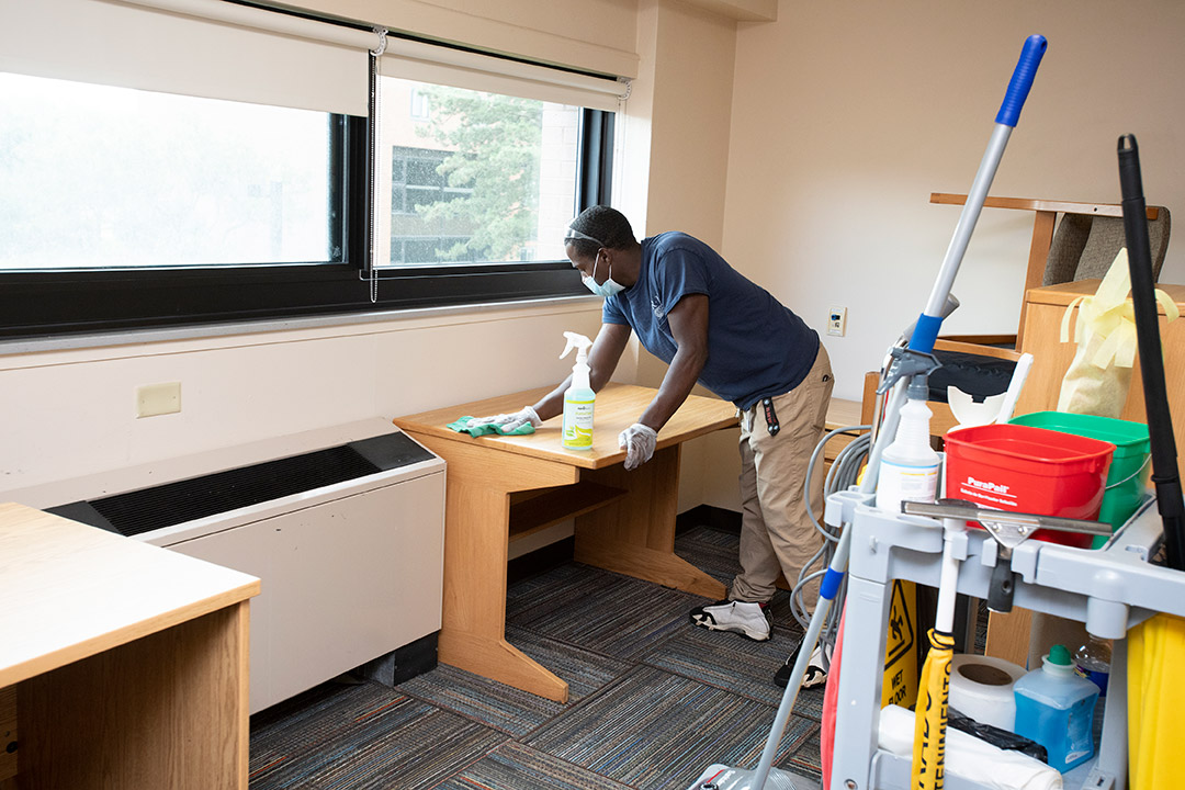 man wearing face masks cleaning a desk in a dorm room.