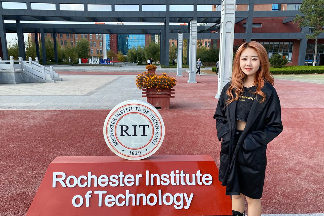 student standing next to RIT logo and sign outside in China.