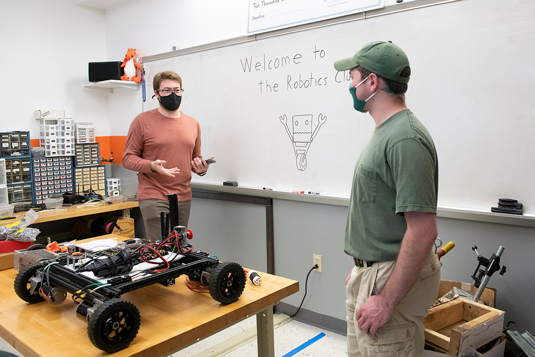 two students working in a robotics lab.