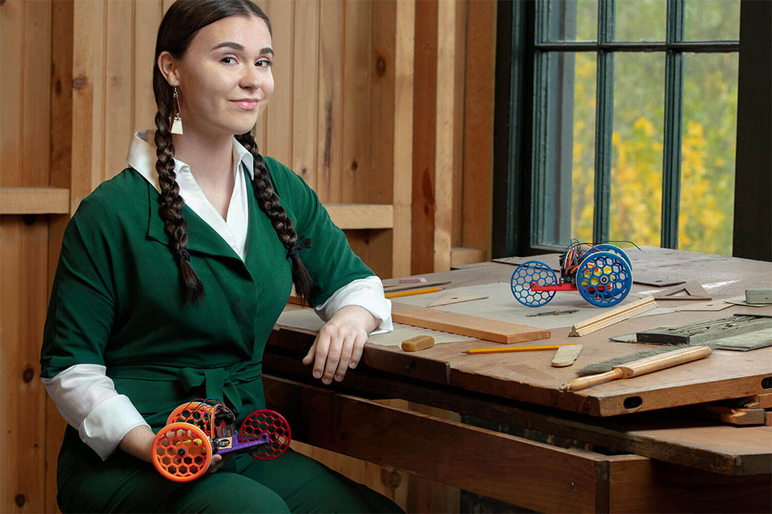 woman sitting at wooden desk holding a small, colorful robotic vehicle.