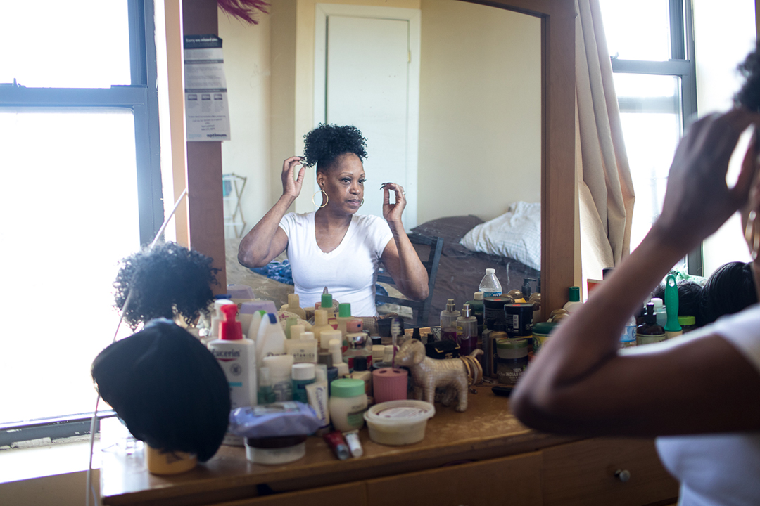 A woman looks into the mirror as she does her hair.