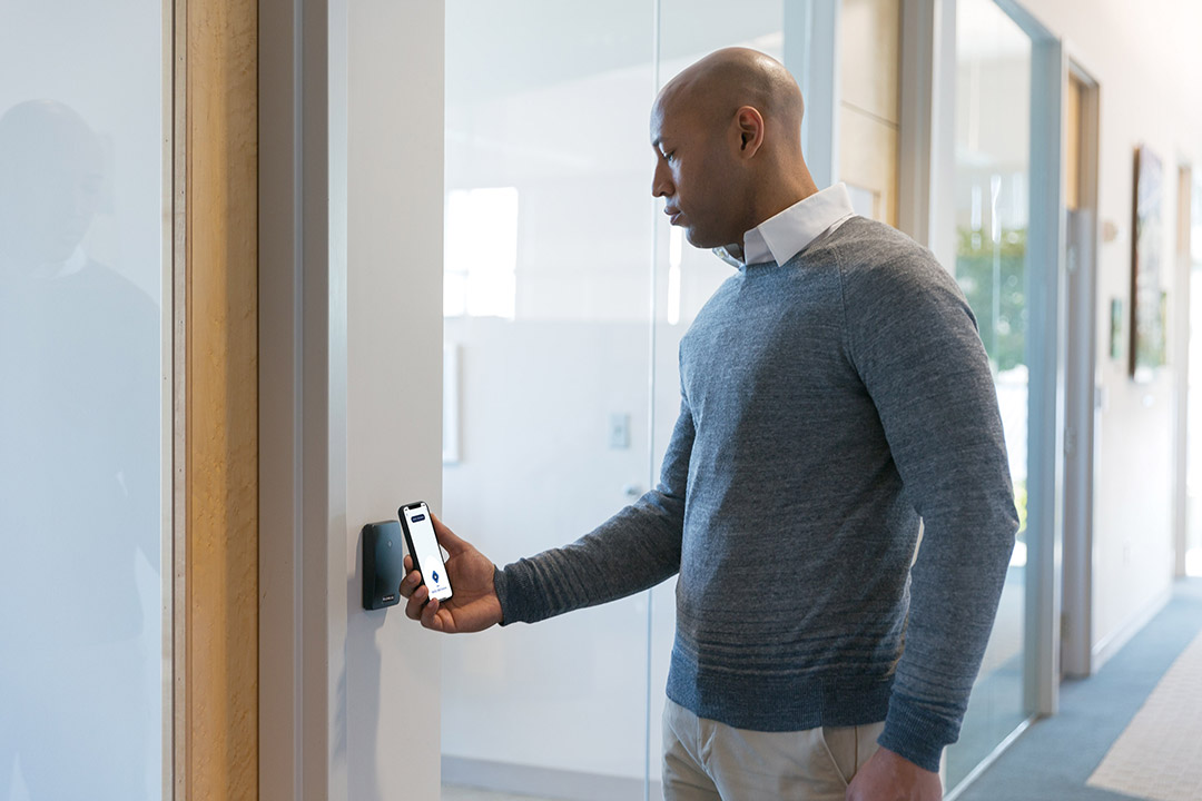 person holding smartphone in front of reader device to unlock a door.