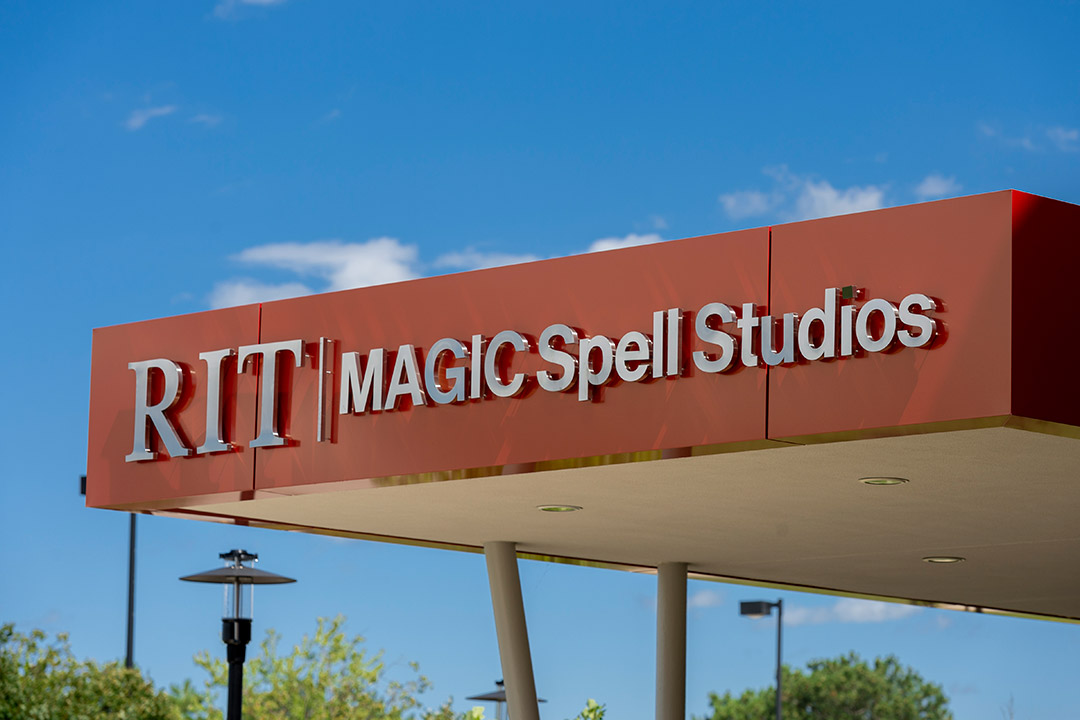 sign on building overhang that reads RIT MAGIC Spell Studios.