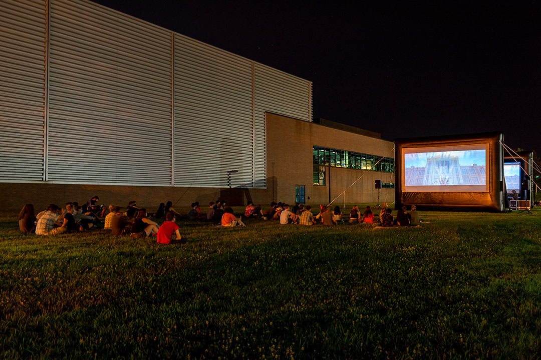 students seated on a lawn attending an outdoor movie at night.