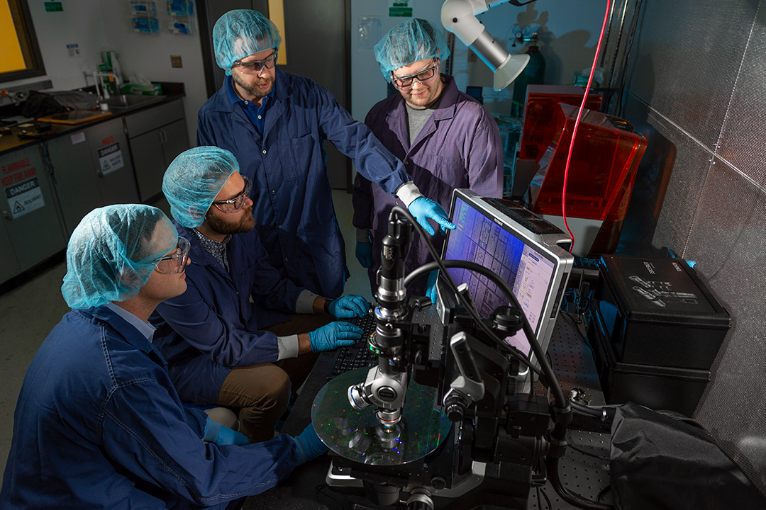 four researchers looking at computer that's analyzing a quantum photonics wafer.