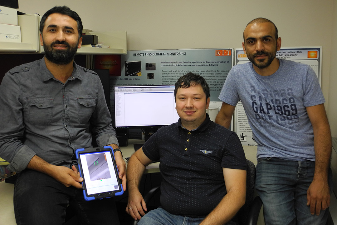 three researchers with one holding a tablet.