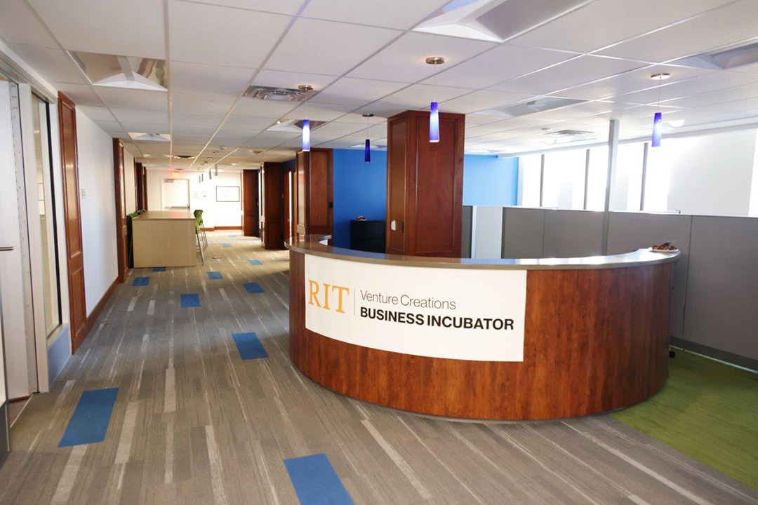 reception desk in an office area with a sign that reads: RIT Venture Creations Business Incubator.