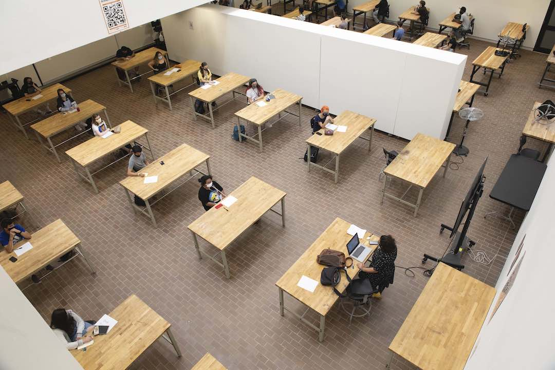 Overhead view of students at tables set up in former gallery space.