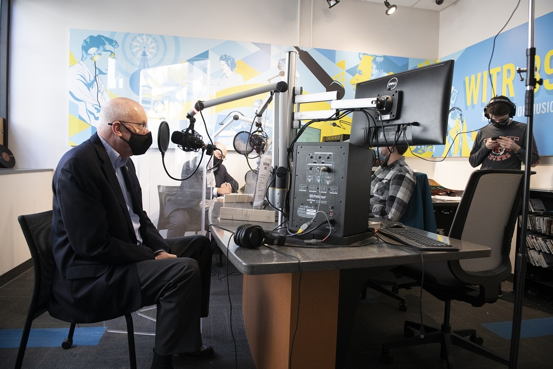 Man wearing a facemask sits in radio studio talking into microphone.
