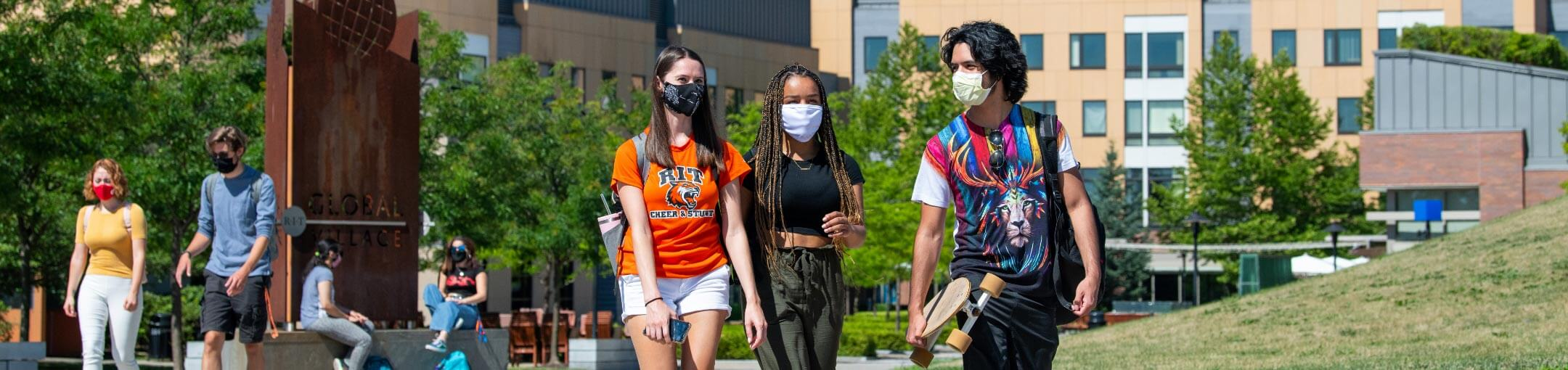 Three students walking through Global Village with other students in the background.