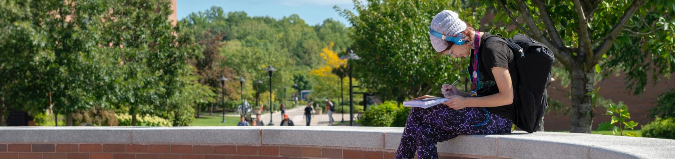 An RIT student sitting on a wall in a quad, writing in their notebook.