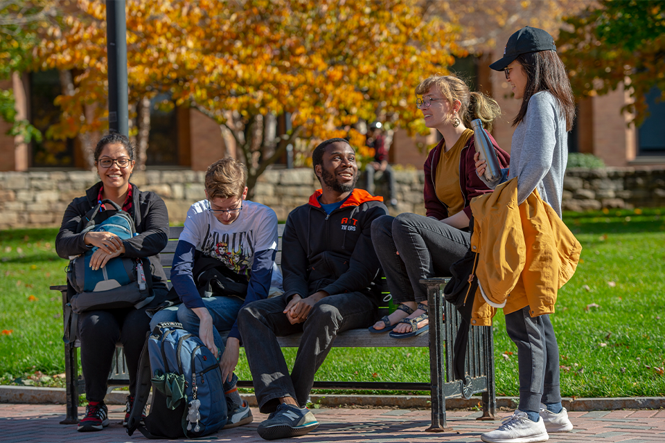 A group of diverse students standing and sitting on a bench talking on RIT campus.