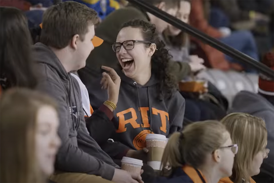 Students laughing at an RIT hockey game