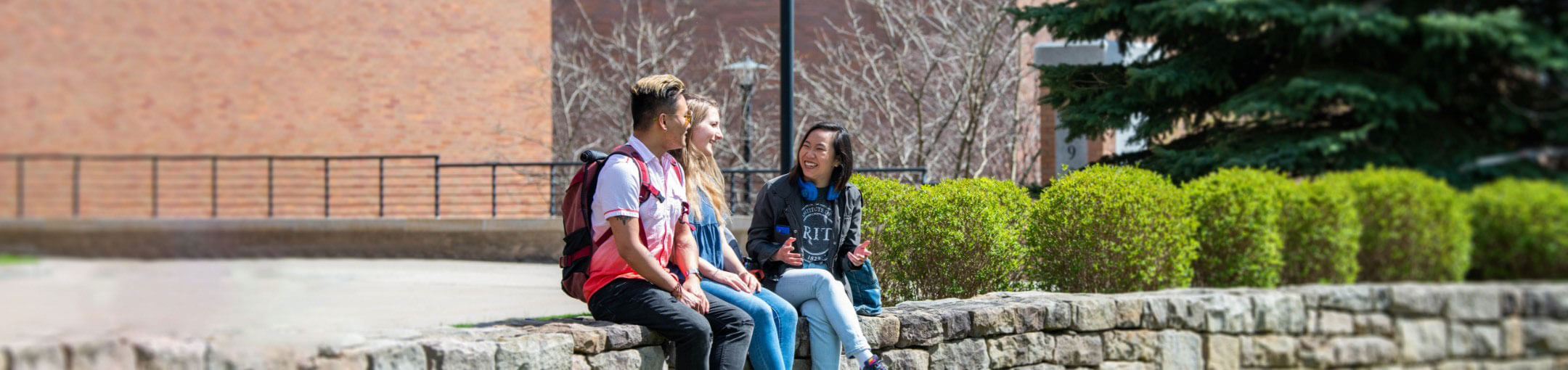 Three RIT students sitting on a stone wall in Kodak Quad.