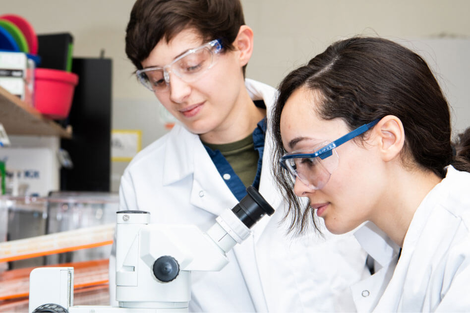 Two RIT students working in a lab.