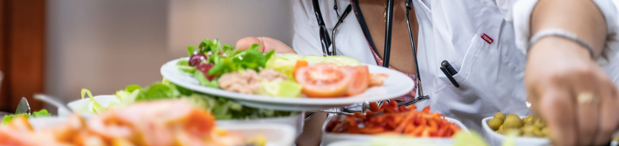 A medical professional adding salad toppings to their plate at a salad bar.