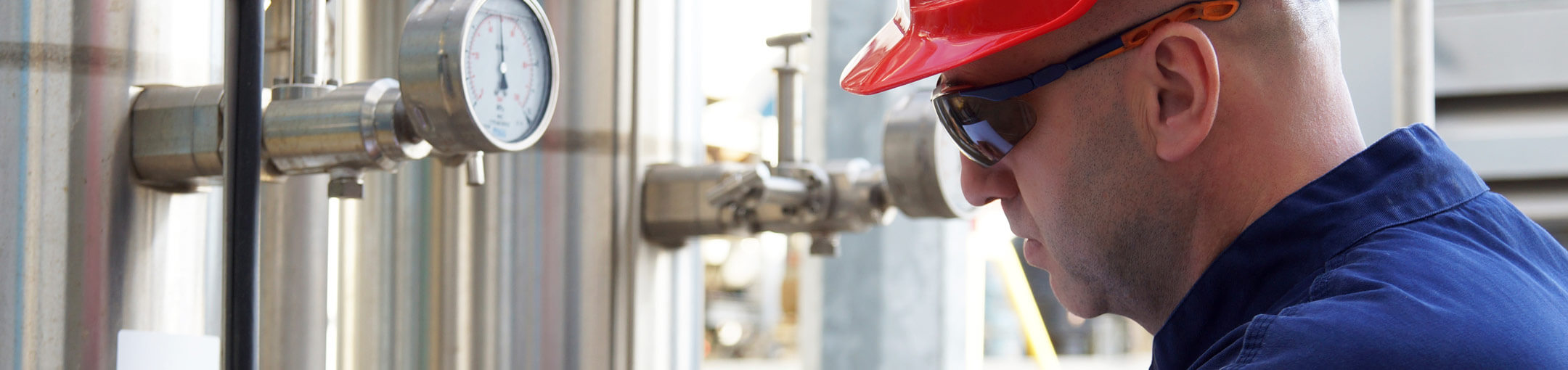 A person wearing a hardhat and eye protection, looking at gauges on equipment.