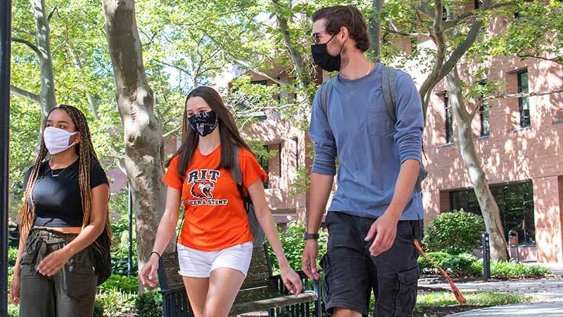 RIT students walking with masks in the infinity quad