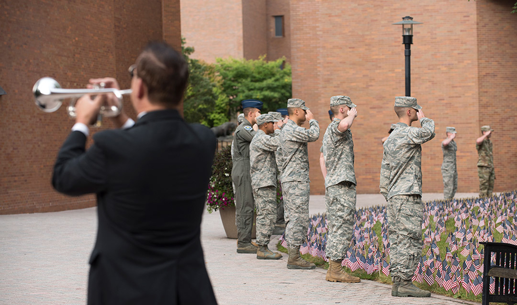 Bugler in foreground, line of ROTC cadets saluting behind