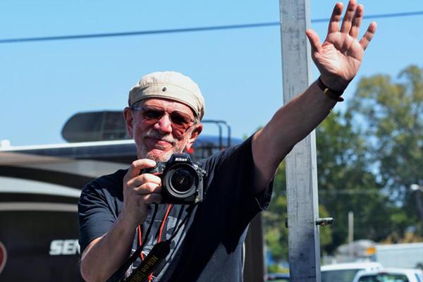 sam holding a camera and waving