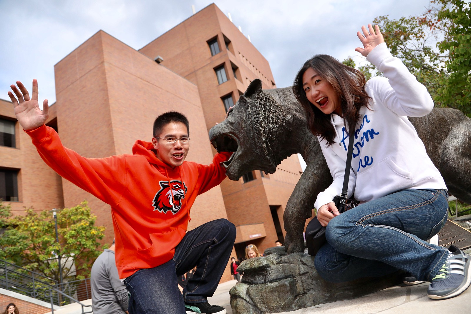 two people with their hands in the air standing next to the tiger statue with the estman building in the background