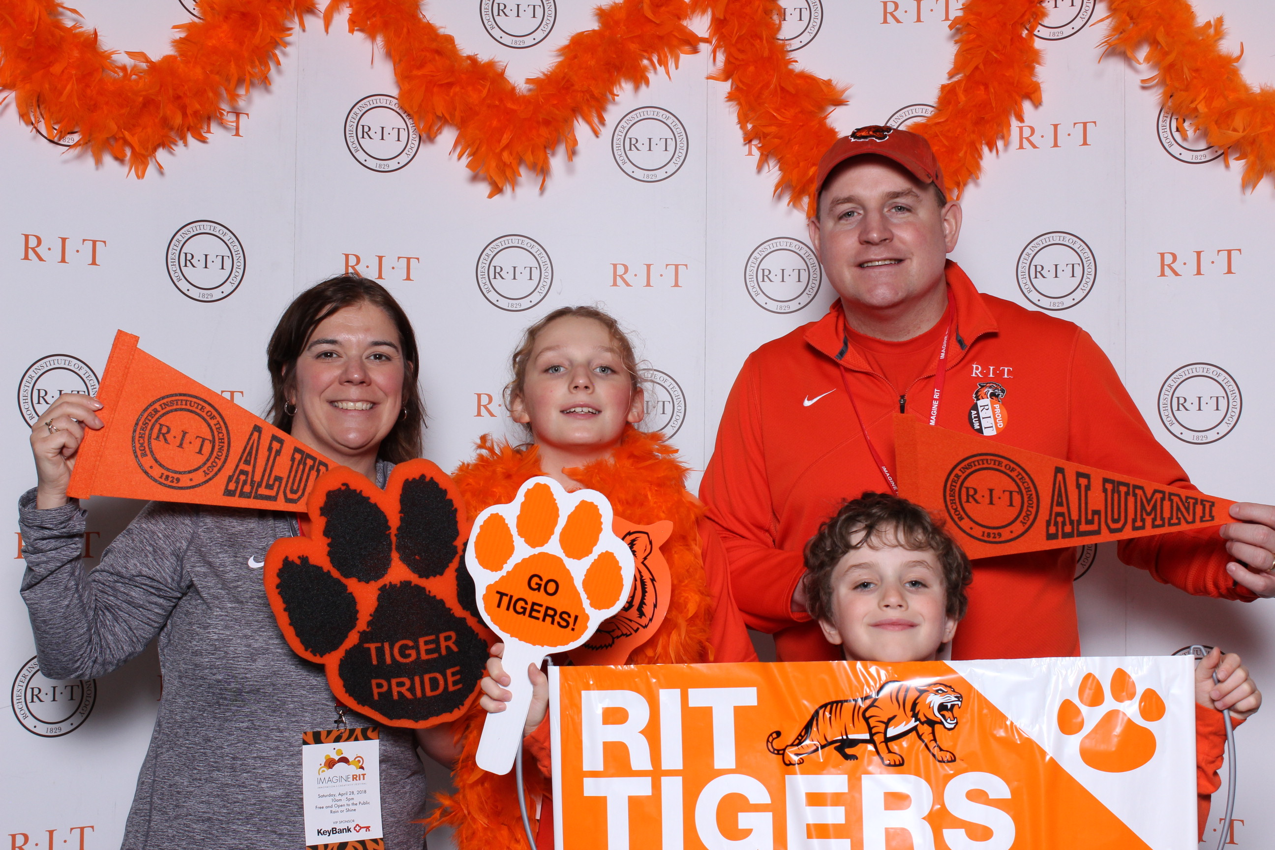 family holding different RIT items (banner, tiger paw, pennant flag)