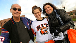 Parents and student smilng wearing RIT gear
