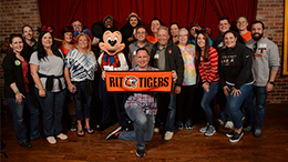image of People standing with mickey mouse holding an RIT Tigers banner