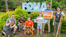 people with shovels rakes and gardening gear standing in front of FOHA sign