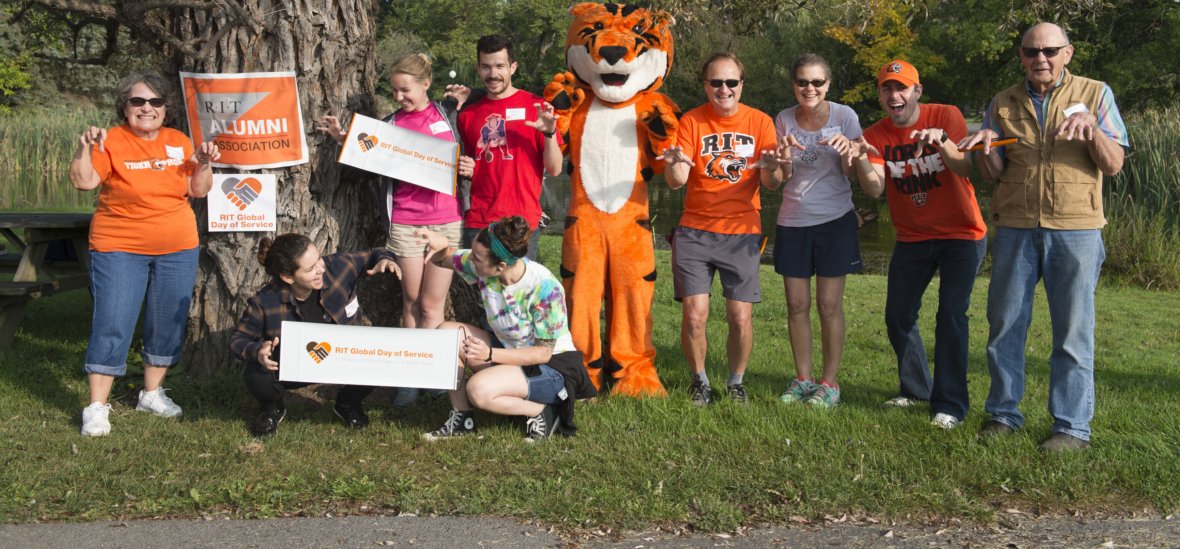 Group of volunteers posing with Richie the RIT Mascot