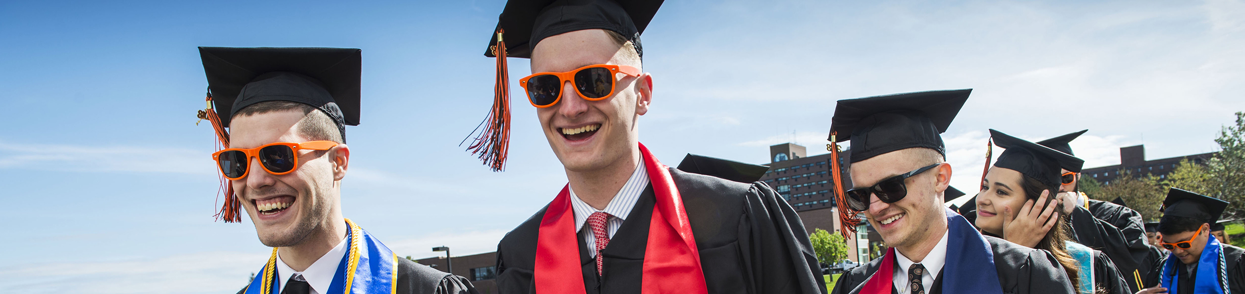 Students dressed in graduation attire and sunglasses