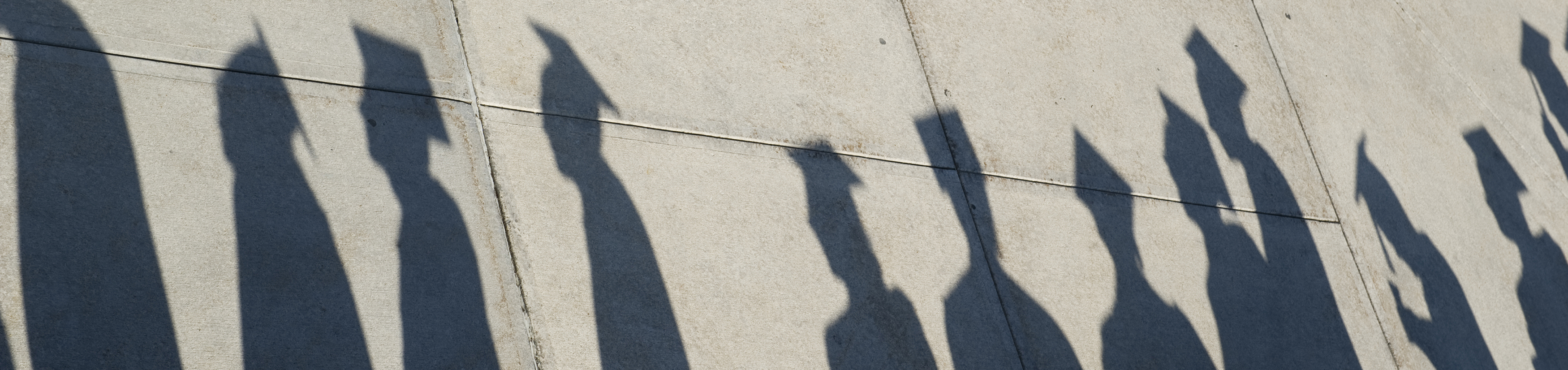 shadows of students in graduate attire