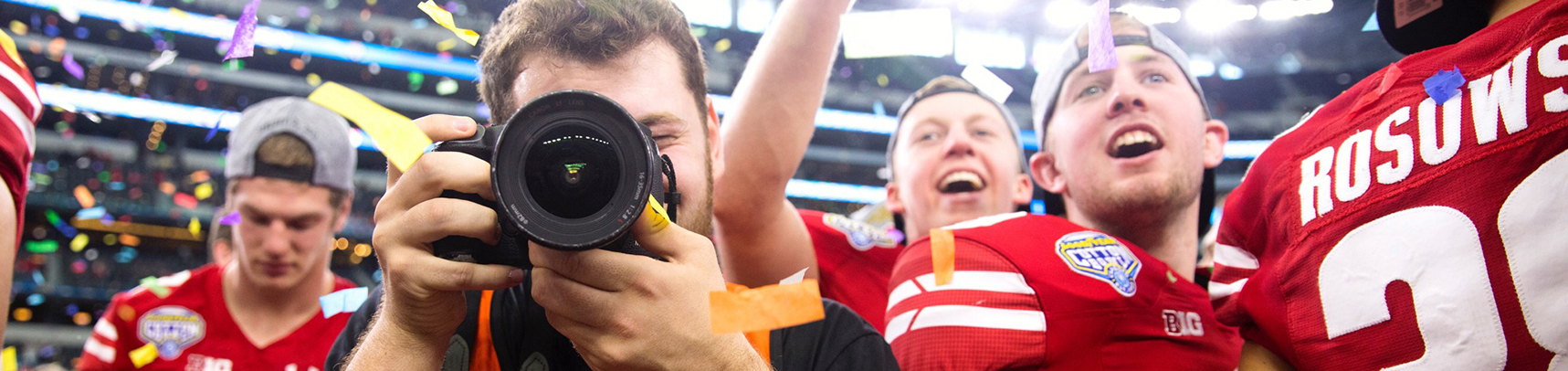 image of a camera man taking pictures at a football game