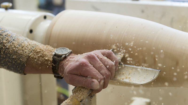 A person turning a piece of wood on a lathe