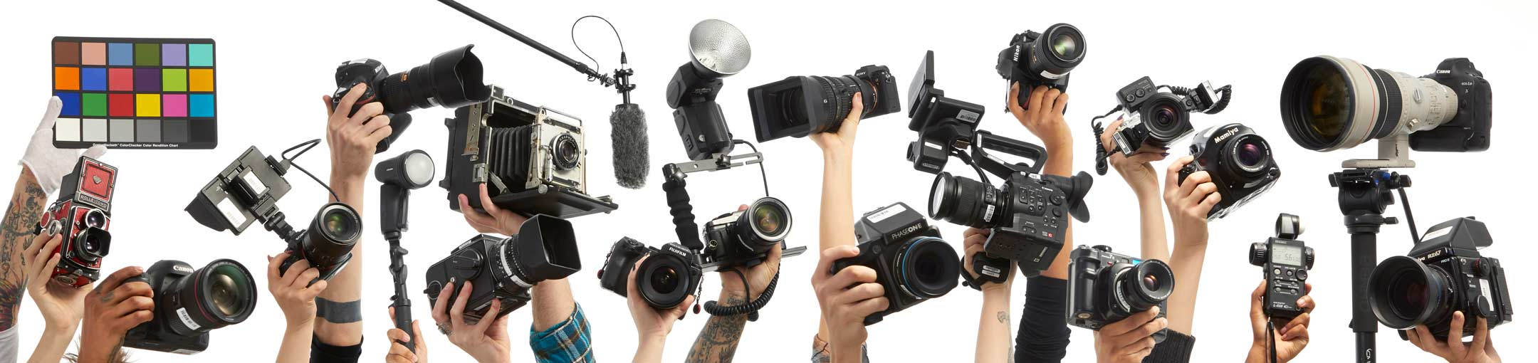 Different cameras being held up by people's hands on a white background