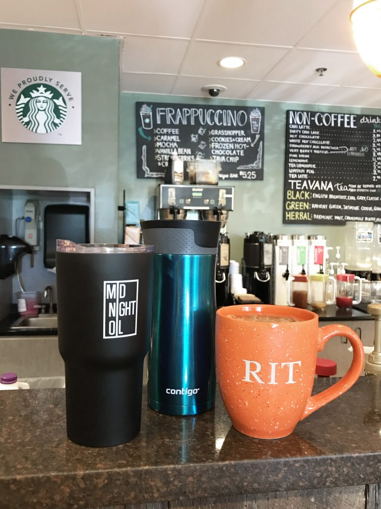Reusable Midnight Oil coffee mug, plain blue reusable coffee mug, and an RIT orange coffee mug on the counter at Midnight Oil.