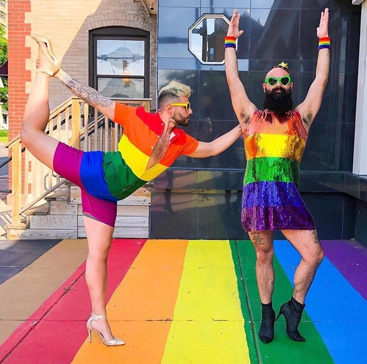 two people doing yoga poses while standing on the rochester park ave rainbow sidewalk and wearing rainbow clothes