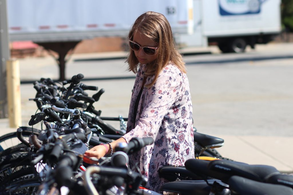 Girl reading a tag on a bike chained up with a bunch of bikes on a bike rack
