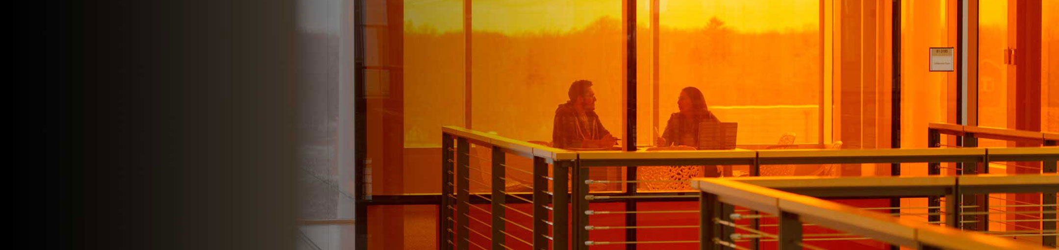 Two people meeting at a table behind an orange glass wall