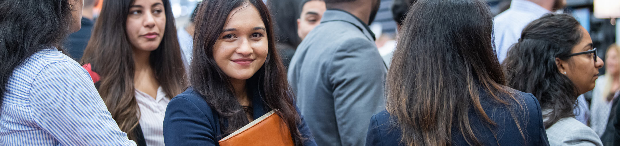 A Female RIT student holding a folder and standing in line at a career fair.