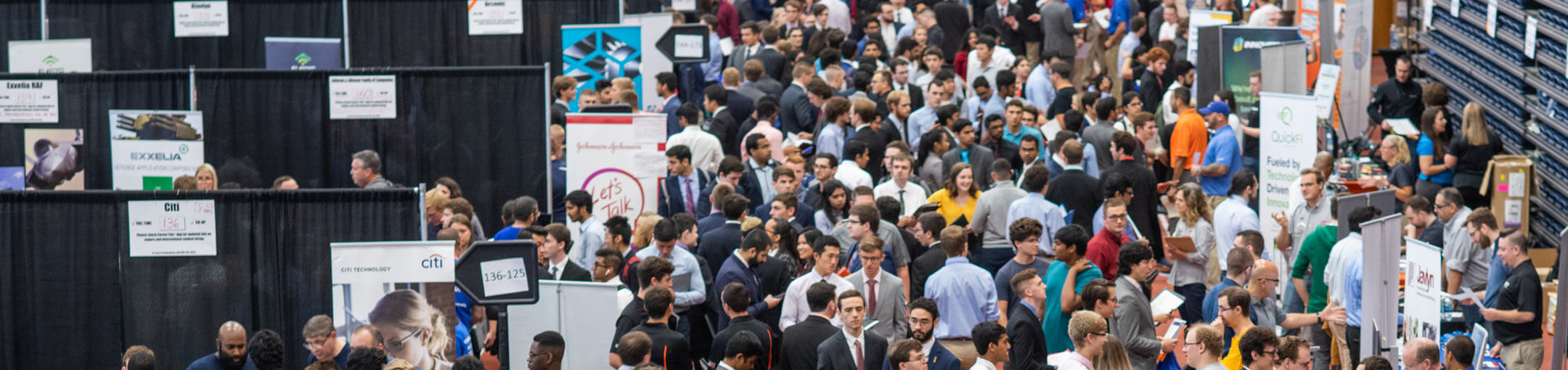 An aerial view of a multitude of students meeting with company representatives at the career fair.