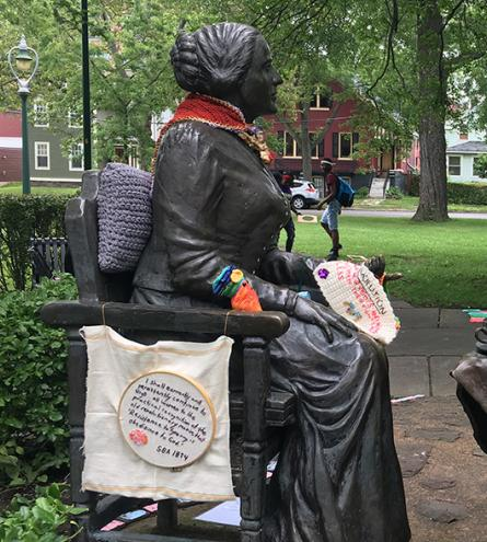 """Yarn installation by Hinda Mandell at """"Let's Have Tea,"""" bronzed sculpture by Pepsy Kettavong depicting Susan B. Anthony and Frederick Douglas, Susan B. Anthony Square Park, Rochester, NY, July 2017. Credit: Tamar W. Carroll"""