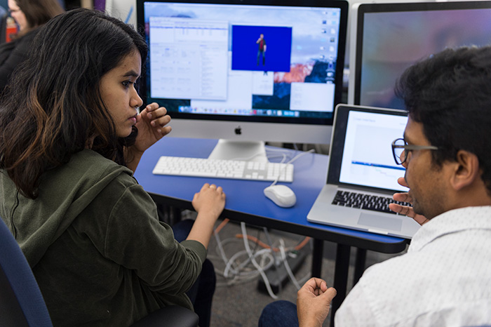 Female student talking to male student in front of a computer