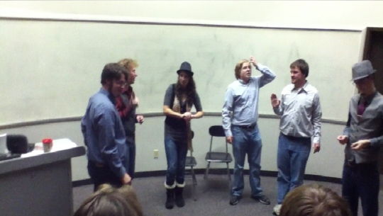 The Improvessionals, standing in a semi-circle, acting.