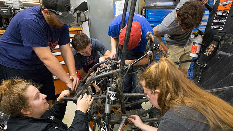 students working on a dune buggy