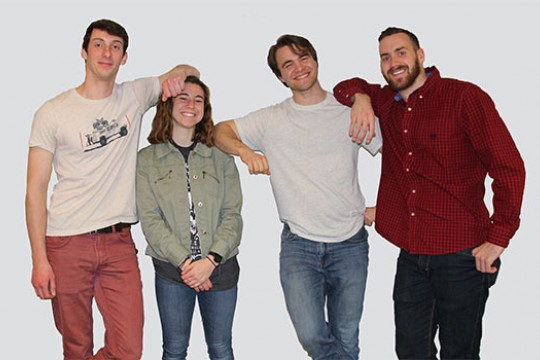 Four members of the Gaia team stand together, posing for a photo by leaning against each other's shoulders with their elbows. James has his elbow on Kerri's head to accentuate their height difference.