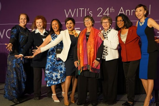Santosh Kurinec and other honorees excitedly pose for a photo, all of them smiling wide and holding their arms out in triumph.