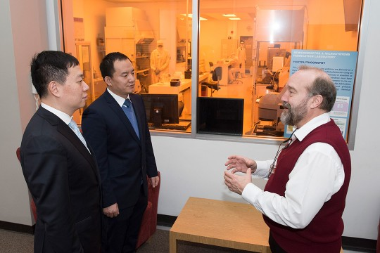 Three men talk outside of cleanroom lab