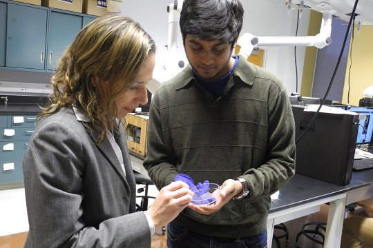 Faculty member and student hold petri dish