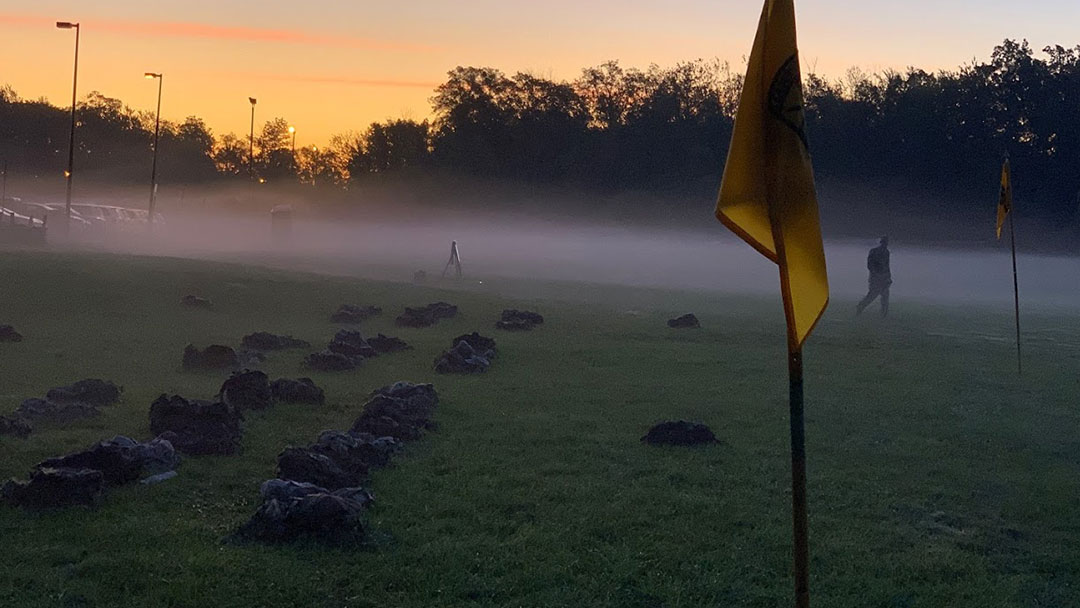 A flag in the foreground of a foggy field.